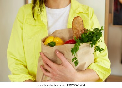 Woman in yellow jacket, standing with shopping paper bag full of fresh fruits and vegetables at home, Concept of online shopping and healthy vegan eating, Space for text