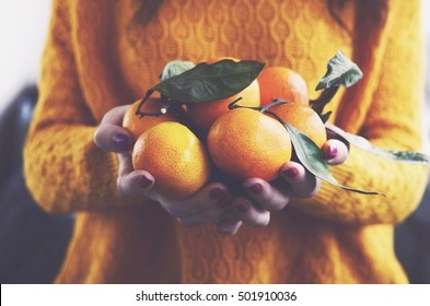 Woman in yellow knitted pullover with ripe clementines in her hands
