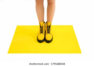 woman in yellow leather shoes from the new collection on a white background Woman's legs in fashionable eco-leather shoes fall-winter 2020. macro photo