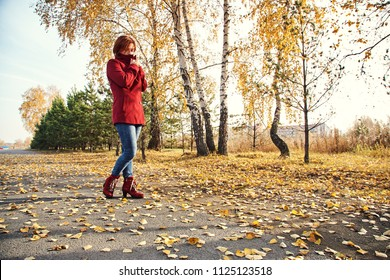 woman with yellow leaves in autumn park