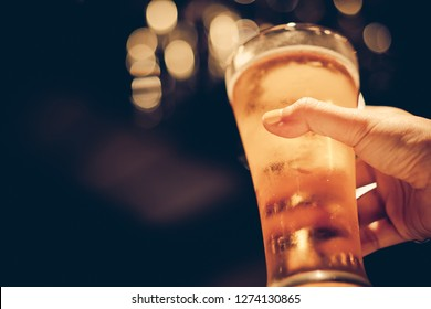 woman with yellow nail polished holding glass of cold beer with beautiful bokeh, dark tone