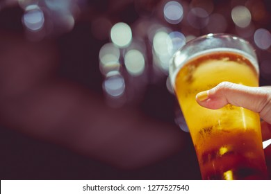 woman with yellow nail polished holding glass of cold beer with beautiful bokeh, retro tone