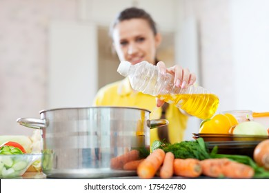 Woman in yellow pours oil from bottle into the pan. Focus on bottle