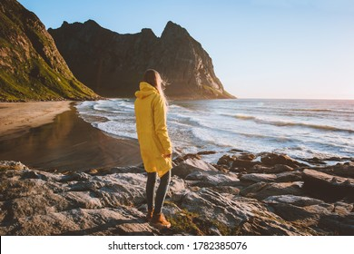 Woman in yellow raincoat walking alone on Kvalvika beach in Norway enjoying ocean view travel lifestyle vacation trip outdoor