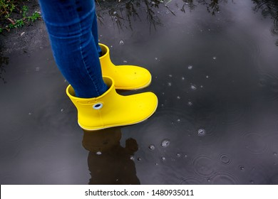 Woman in yellow rubber boots standing in the puddle.