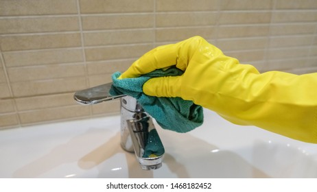 Woman in yellow rubber gloves cleaning a water tap. Housewife holding a rag. White sink. Modern bathroom. Cleaning company services. Housemaid washes the apartment.