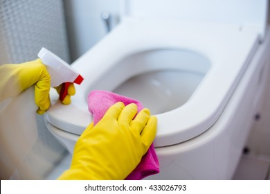 Woman in yellow rubber gloves cleaning toilet with pink cloth