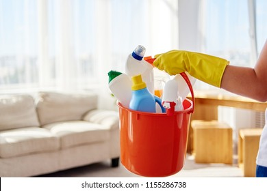 Woman in yellow rubber gloves holding in hand cleaning products in orange  bucket in living room at home, copy space. Housework, cleanig and chores concept