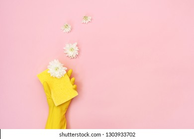 Woman in yellow rubber gloves showing small sponge for washing in her hand isolated on pastel pink background with white flowers and empty space for text