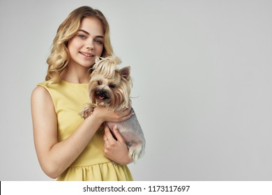a woman in a yellow sarafan holds a dog in her hand