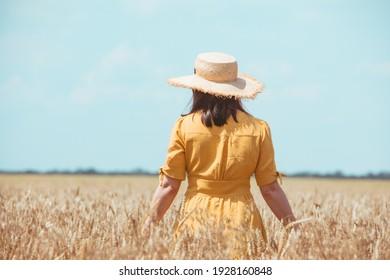 woman in yellow sundress walking by wheat field. summer time