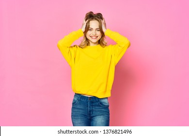 A woman in a yellow sweater touches her head with her hands on a pink background