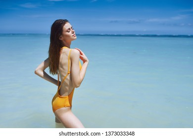 A woman in a yellow swimsuit is standing in the clear water of the sea