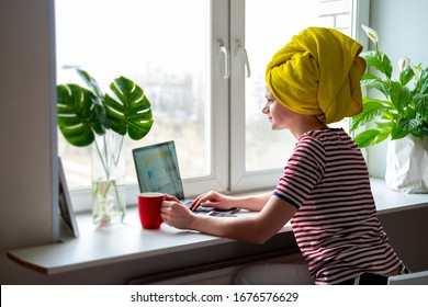 Woman with yellow towel on head is working office work remotely from home on bed. Using computer. Distance learning online education and work