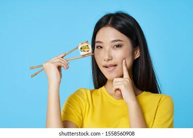 Woman in yellow T-shirt holds chopsticks sushi rolls Japan