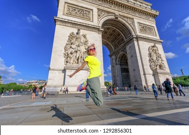 Woman with yellow vest jumping at Arch of triumph. Popular landmark in Paris, France. Concept of happiness for the triumph of people's protests. Gilets Jaunes are symbol of Parisian protest movement.