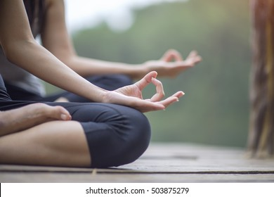 Woman yoga finger acting on hands in soft focus background with Nature surrounding