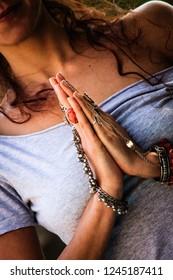 woman in yoga meditation outdoor shot closeup with lot of rings and bracelets