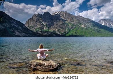 Woman in yoga pose meditating by lake. Jenny Lake in Grand Tetons National Park, Jackson, Wyoming.