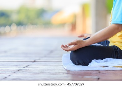 Woman yoga pose at the park. Focus on hand
