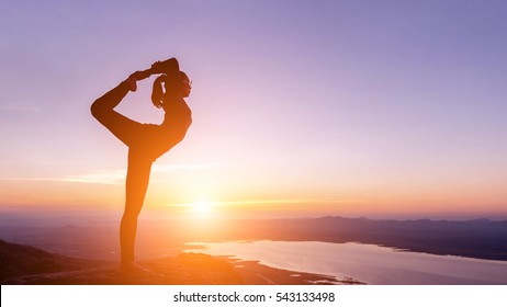 The woman with yoga posture on the mountain at sunset; Silhouette of gorgeous young woman practicing yoga outdoor.