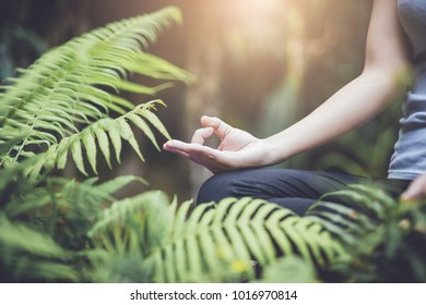 Woman Yoga - relax in waterfall nature.