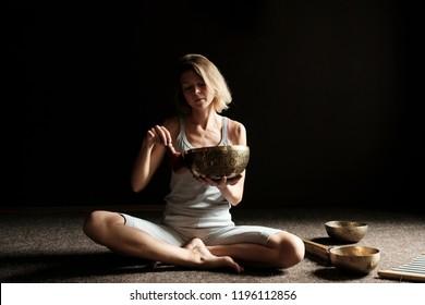 Woman the yogi plays on the Tibetan singing bowl. Tibetan Singing Bowls
