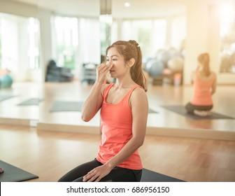 woman yogi practicing yoga, sitting in Padmasana, Lotus pose, using Alternate Nostril Breathing, nadi shodhana pranayama, working out,in yoga studio