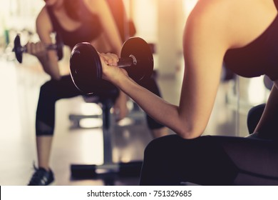 Woman young asian holding dumbbell without rack for workout exercise muscle building strong heavy weight in fitness gym and healthy lifestyle