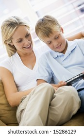 Woman and young boy in living room with handheld video game smiling