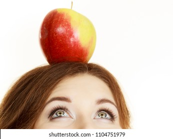 Woman young female holding big red green apple fruit on top of head looking up. Healthy eating, vegetarian food, dieting concept.