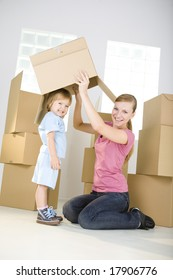 A woman with young girl are between cardboard boxes. A woman taking off cardboard box from head young girl. They're looking at camera.