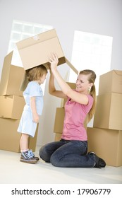 A woman with young girl are between cardboard boxes. A woman taking off cardboard box from head young girl.