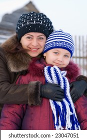Woman with a young girl in a cap and scarf