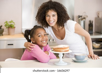 Woman and young girl in kitchen with cake and coffee smiling