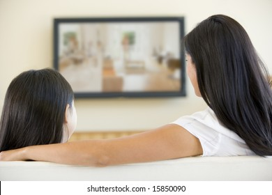 Woman and young girl in living room with flat screen television