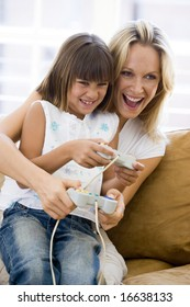 Woman and young girl in living room with video game controllers smiling