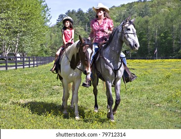 A woman and a young girl on horseback riding in the pasture.