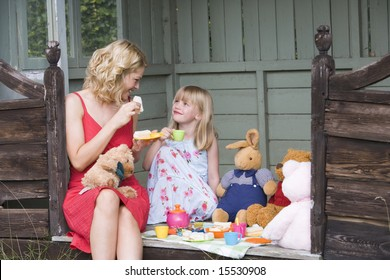 Woman and young girl in shed playing tea and smiling