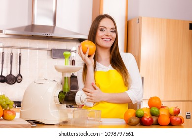 Woman young housewife in kitchen with fruits and juicer preparing to make fresh juice. Healthy eating, cooking, vegetarian food, dieting and people concept.