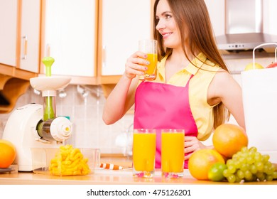 Woman young housewife in kitchen at home drinking fresh homemade orange juice drink. Healthy eating, vegetarian food, weight loss and people concept.