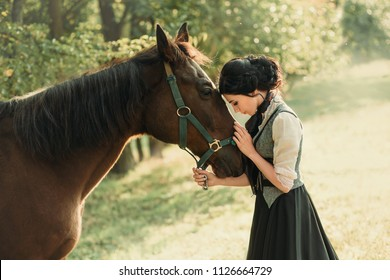 Woman young lady. elegant vintage dress, tenderness affection hugs embrace brown horse stroking face animal love. ancient retro collected hairstyle. green nature blurred bokeh background. Art photo