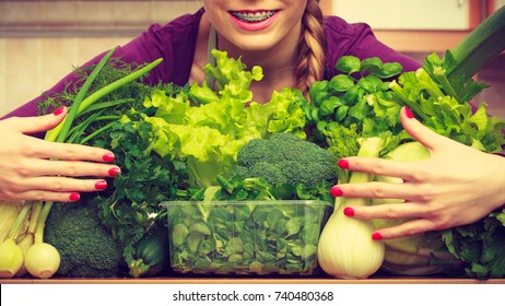 Woman young positive housewife in kitchen with many green leafy vegetables, fresh produce organically grown on counter. Healthy lifestyle, cooking, vegetarian food, dieting and people concept.