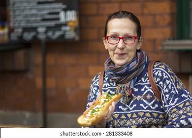 Woman with Zapiekanka (Polish casserole)