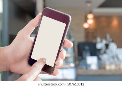Womanan using smartphone with blurred coffee shop, stock photo