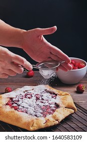 Womanan's hands close-up sprinkling fresh baked strawberry pie with icing sugar, dark toned photo