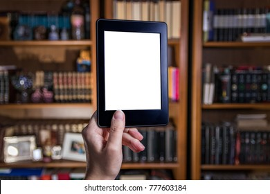 Womand hand holding ebook in front of bookshelves