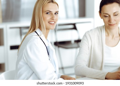 Woman-doctor sitting and communicating with her female patient in clinic. Blonde physician happy to help. Medicine concept