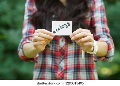 """woman-ecologist or biology student holding a piece of paper with """"ecology' note in her hands on greenery background, selective focus"""