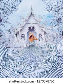 Woman(girl) with a beautiful white dress flying around and yellow hat looking to the White Temple (castle) (Wat Rong Khun) in Thailand covered in white snow.